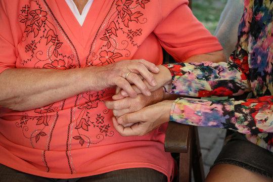 Großmutter hält die Hände von Ihrer Enkelin