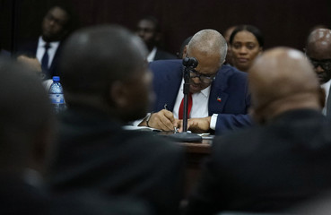 Haitian Prime minister Jack Guy Lafontant writes during a meeting with members of the Parliament in Port-au-Prince