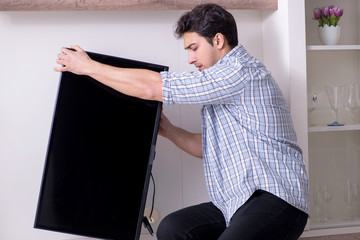 Man repairing broken tv at home
