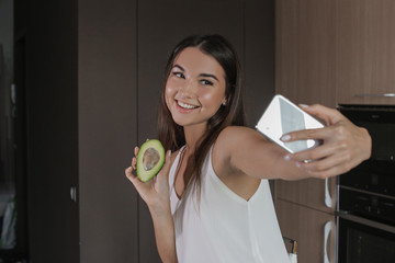 girl photographed on the phone with vegetables in the kitchen, healthy food