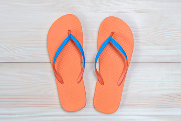 Orange flip flops isolated on wooden background. Top view