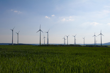 Windmills on a green field in the summer in front of a blue sky