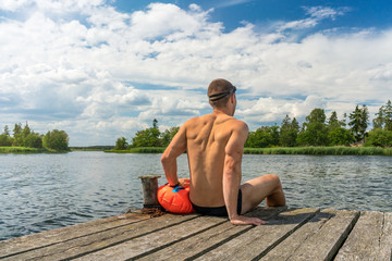 Sexy young man on a jetty with a drybag and goggles, open water swim