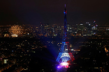 Fireworks explode in the sky near the Eiffel Tower, lit in blue, white and red lights, in a picture taken from the Montparnasse Tower Observation Deck, at the end of Bastille Day events in Paris
