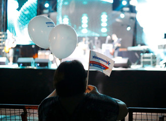 """An attendee holds flags and balloons with the message """"Macedonia in NATO and the EU"""" during events organized by the government in 15 towns to celebrate an invitation for Macedonia to join NATO, in Skopje"""