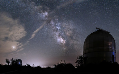Domes of small telescopes in an observatory in the background of the milky way