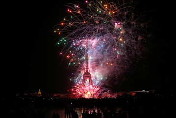 Fireworks explode in the sky above the Eiffel Tower at the end of Bastille Day events in Paris