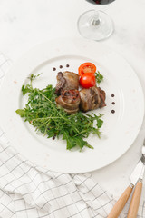 Meat rolls served with fresh arugula and tomato on white plate
