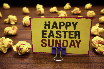 Handwriting text writing Happy Easter Sunday. Concept meaning Greeting someone about holidays Spring is coming Yellow sticky card clipped text notice crumpled paper balls wood table.