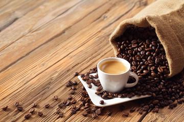 Espresso Kaffee Tasse mit Kaffeebohnen und altem Holz Tisch Hintergrund