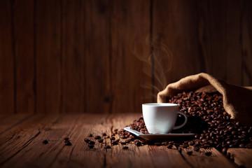 Espresso Kaffee Tasse mit Kaffeebohnen und altem rustikalen Holz Tisch Hintergrund