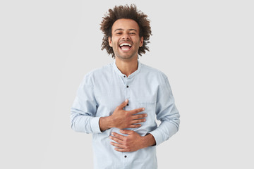 Positive mixed race male touches stomach, can`t stop laughing, being in good mood, hears funny stories from interlocutor, expresses happiness, dressed elegantly, isolated on white background