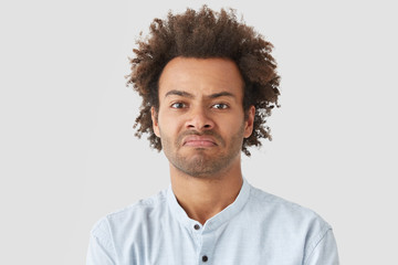 Negative human facial expressions concept. Curly African American male purses lips, has angry look, being dissatisfied with not delicious supper cooked by wife, suggests go in restaurant instead