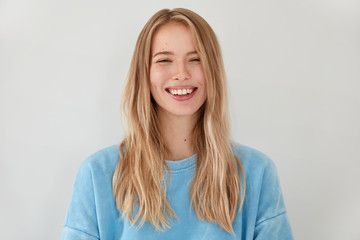 Smiling satisfied female with broad shining smile, feels happiness after successful graduation, wears casual outfit, stands against white background. Glad woman rejoices unforgettable journey