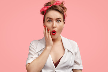 Emotive pinup girl with stupefied expression, being amazed by sudden news, opens mouth widely, can`t believe in fault, isolated over pink background. Surprised young woman in retro style clothes