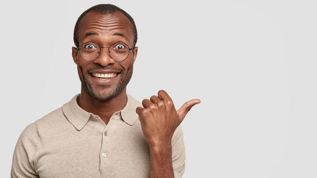 Joyful African American male with healthy dark skin, points at something very beautiful and appealing aside, wears casual t shirt and round spectacles, isolated over white background, free space