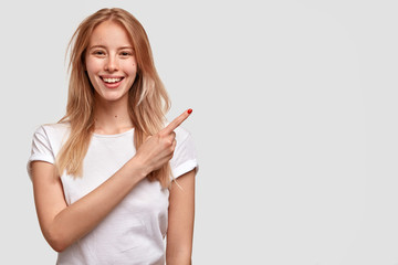 Wall Mural - Cheerful European female with broad smile, appealing look, points aside, dressed in casual white t shirt, shows something pleasant, advertises new item in shop, copy space for your text or promotion