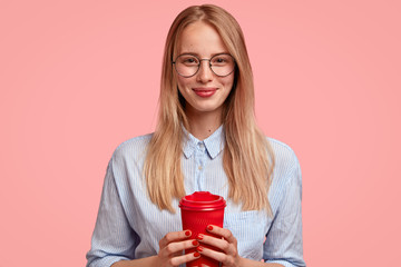 Wall Mural - Horizontal shot of pleasant looking female student has coffee break, holds takeaway red cup, wears round spectacles and shirt, enjoys conversation with friend, isolated over pink background.