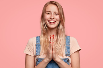 Wall Mural - Indoor shot of good looking young long haired female has broad shining smile, keeps palms pressed together, begs for something in her boyfriend, isolated over pink background. Please, forgive me