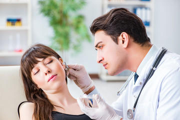 Doctor checking patients ear during medical examination