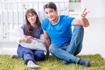 Young parents with their newborn baby sitting on the carpet
