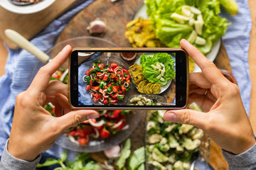 Smartphone food photography of vegetarian lunch or dinner. Woman hands taking phone photo of food in trendy style for social media or blogging.