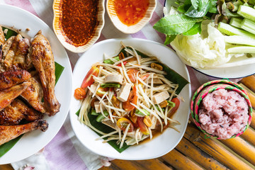Top view of papaya salad and grilled chicken in white plate on bamboo background