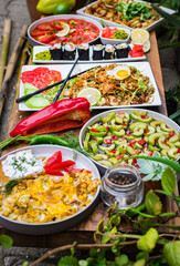 Full asian Thai cafe menu on wooden table. Authentic Indonesian traditional food. Vegetables salad, sushi rolls, fried omelet, fried rice, wok, wasabi, soy sauce. Thailand noodle, chopsticks.