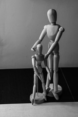 Two wooden movable mannequins of different sizes stand side by side. Shooting close-up.