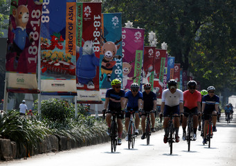 Cyclists ride past banners promoting the upcoming Asian Games in Jakarta