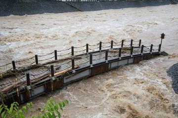 河川の増水で流されそうな橋