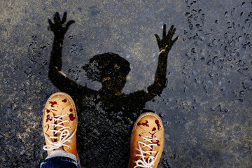 Scary Zombie Man with Dropped Blood on Shoes Raise up Creepy Hand. present by Reflection Shadow on the Ground after stopped Raining for Halloween Day or Horror story