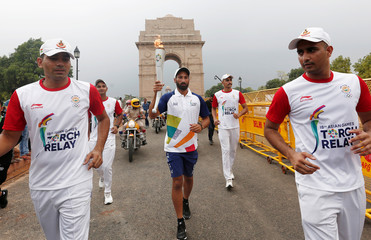 Former Indian hockey team player Sardar Singh takes part in the 2018 Asian Games torch relay in front of the India Gate in New Delhi
