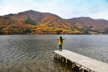 Travel in Fall Season Concept. Happy Traveler Woman Raise Up Arms and Standing on Wooden Waterfront over the Lake. Red and Yellow Foliage on the Mountains as background
