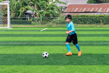 Asian boy playing football at the stadium, sports, outdoor activities