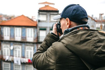 A professional travel photographer or tourist photographs a beautiful cityscape in Porto in Portugal. Professional occupation or hobby