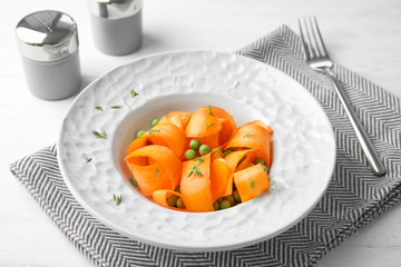 Tasty salad with fresh carrot in plate on table