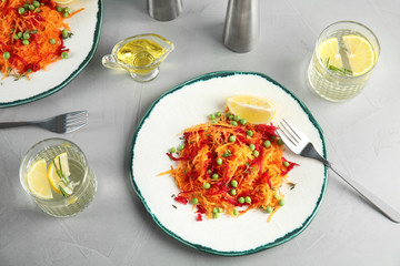 Plate with tasty carrot salad on table, top view