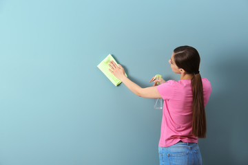 Young woman cleaning color wall with rag