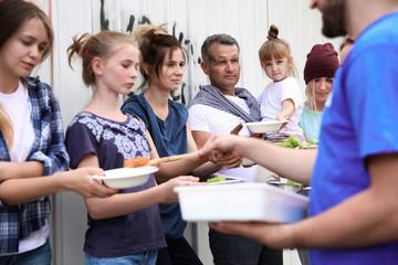 Poor people receiving food from volunteers outdoors