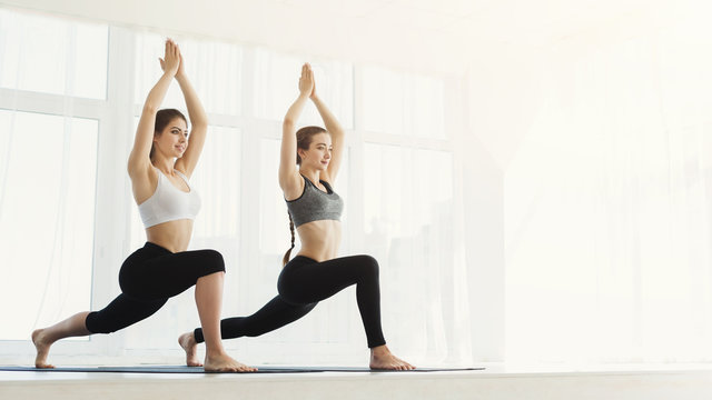 Two sporty women practice yoga in light gym