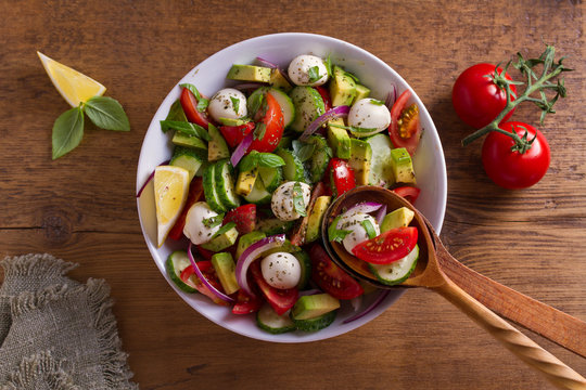 Avocado, tomato, cucumber salad with mozzarella cheese. View from above, top studio shot