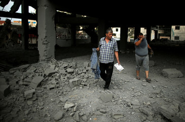 Palestinians inspect a building that was destroyed by Israeli air strikes in Gaza City