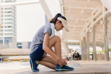 Young beautiful Asian model woman jogger running in morning.