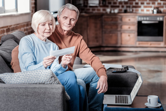 Having rest. Handsome grey-haired man embracing his woman while sitting on the sofa