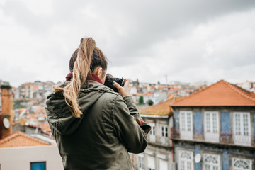 A professional travel photographer or tourist photographs a beautiful cityscape in Porto in Portugal. Professional photography or interesting hobby.