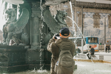 A professional photographer or videographer takes pictures or shoots a video of a beautiful fountain on the square in Porto in Portugal or a tourist makes a photo or video for memory