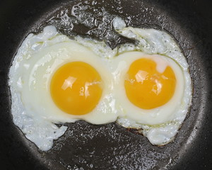 Close up two fried eggs on black pan background
