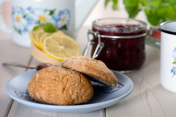 The cookie on the paper mat is next to the slices of lemon and jam in jar on the table
