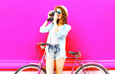 Cool girl with retro camera and bicycle over colorful pink background in profile